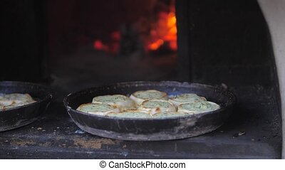 small pizza baking in the oven burning fire. slow motion video. the cook prepares pastries on an open fire. baking lifestyle in the oven with fire concept cooking
