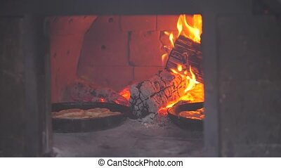 small pizza baking in the oven burning fire. slow motion video. the cook prepares pastries on an open fire. baking in lifestyle the oven with fire concept cooking