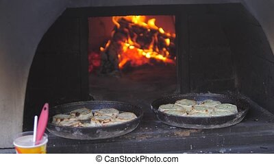 small pizza baking in the oven burning fire. slow motion video. the cook prepares pastries on lifestyle an open fire. baking in the oven with fire concept cooking