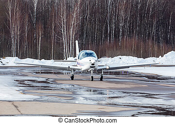 Small plane at the airport in winter