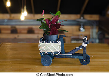 Small plant in flower pot on wooden table