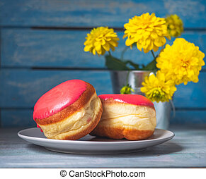 Small plate of donuts with strawberry frosting and a bouquet of yellow flowers, in a tin bucket