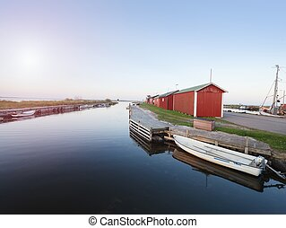 Small port at fishing village with boats. Quiet bay at stony dam. Summer traveling in Sweden.