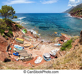 Small port with fishing boats. View over sea and mountains.