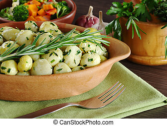 Small potatoes with herbs, such as parsley, thyme and rosemary with a fork; with fried vegetables, garlic and fresh herbs in a wooden mortar in the background (Selective Focus, Focus on the rosemary b