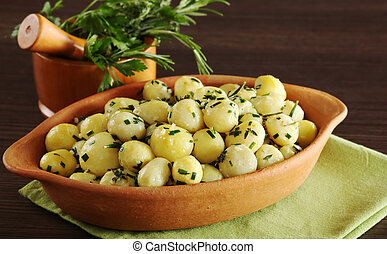 Small potatoes with herbs, such as parsley, thyme and rosemary with a mortar filled with herbs in the background (Selective Focus, Focus on the front of the potatoes and the bowl)
