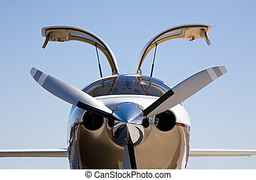 small private aircraft with doors up, against blue sky with limited dof