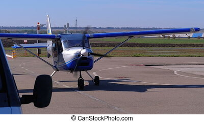 Small Private Airplane with a Rotating Propeller Standing on...