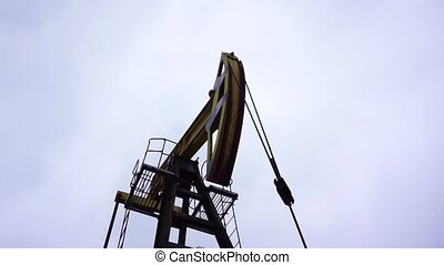Small private yellow derrick pumps oil on the field. Development of minerals.