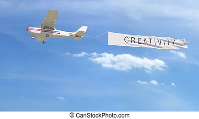 Small propeller airplane towing banner with CREATIVITY caption in the sky. 4K clip
