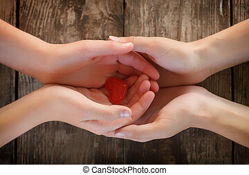small red heart lies in the hands of men and women, the concept of love and romance