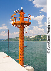 Small red lighthouse on harbor entrance of Balchik, against great blue sky with waves crashing the shore