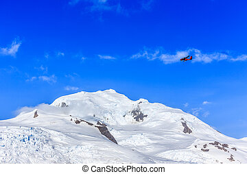 Small red plane flying among clouds over snow peaks and glaciers, Hald Moon island,  Antarctic peninsula