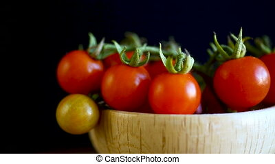 small ripe red cherry tomatoes in a wooden bowl on a table