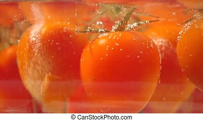 Small ripe tomatoes boiling in a glass pan