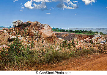 small rock hill near the road with blue sky
