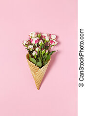 Small roses in waffle cone on pink background, copy space. Minimal style flat lay. For greeting card, invitation. March 8, February 14, birthday, Valentine's, Mother's, Women's day concept. Top view