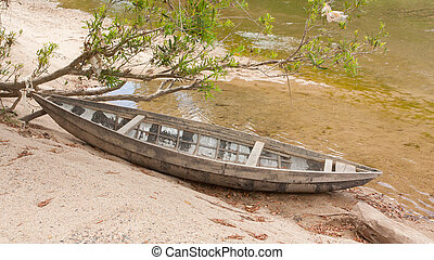 Small rowing boat on the shore of a small river