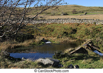 Farm water storage dam with weir amoungst moorland with stone wall and trees.