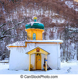Small russian church at sunset in winter landscape