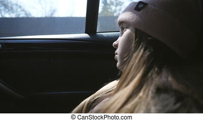 Small sad girl rides on car at countryside and watches at nature through the glass of auto. Little female kid with long blonde hair sits in backseat of a moving SUV and looks through the window
