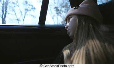 Small sad girl with long blonde hair looks outside through the window in the backseat of a moving SUV. Beautiful female child rides on car and watches at nature through the glass of auto. Low view