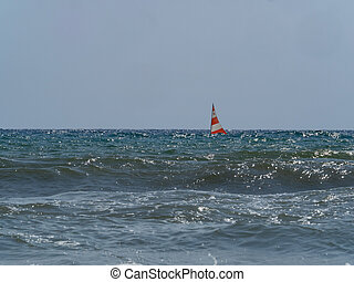 small sailing boat in  the waves of the rough sea