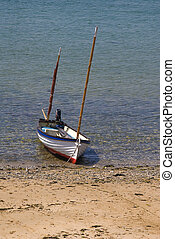 Small sailing boat on the beach