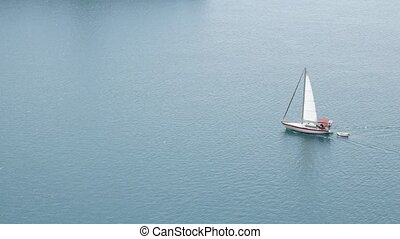 Small sailing yacht sailing in the sea, aerial top view.