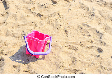Small sand pail toy on summer beach.