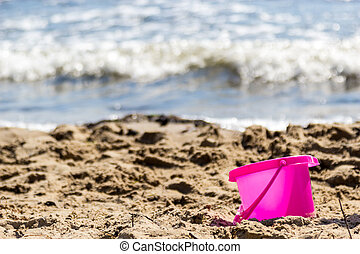 Small sand pail toy on summer beach. Holiday vacation.