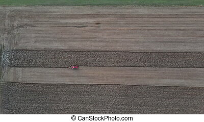 Small scale farming with red tractor plowing plow in preparing land for sowing field
