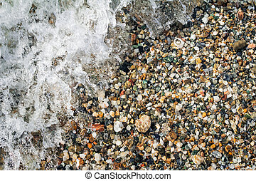 Small sea stones on the seashore, covered with a sea wave.
