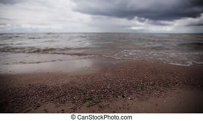 Small sea waves on beach with tiny stones. Grey cloud sky. Summer. Slider pan.