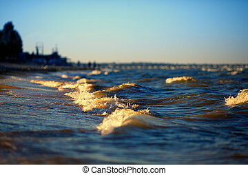 Small sea waves gently swapping on sandy beach