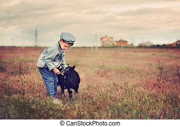 small shepherd - the boy in a cap in the field grazes goats