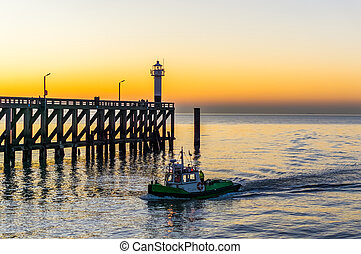 small ship sailing in the harbor of Blankenberge, Belgium, the jetty with lighthouse in the background, colorful sky at sunset