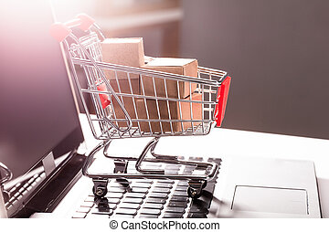 Shopping Cart With Cardboard Boxes On Laptop