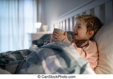 Small sick toddler girl lying in bed indoors at home, holding cup.
