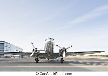 Small silver airplane parked in an airport