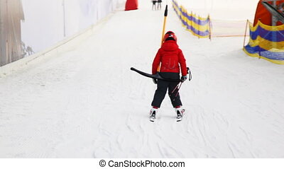 small skier boy sitting on handle goes down hill in sport center