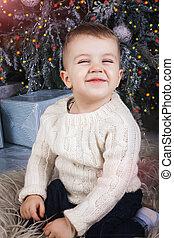 small smiling boy sitting near the christmas tree