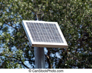 small solar panel on pole with trees