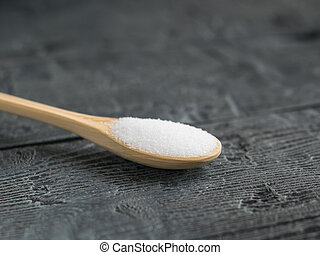 Small spoon of light wood with salt on the dark wooden table.