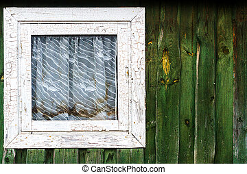 Small square window on green plank wall