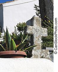 small stone cross in the garden of greek monastery