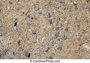 Small stones on yellow sand close up