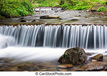 Small stream waterfall on spring forest