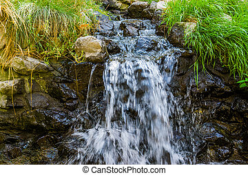 small streaming waterfall, water flowing over rocks, beautiful nature background