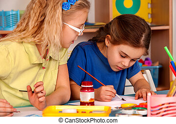 Small students children painting in art school class.